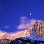 The moon rests over Mount Lougheed.
