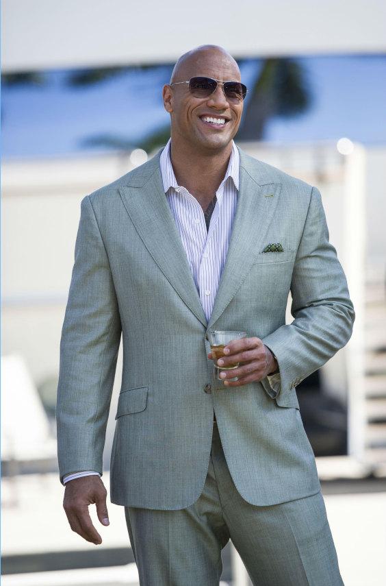 The Rock com terno verde claro elegante, com camisa de listras lilases e sem gravata.