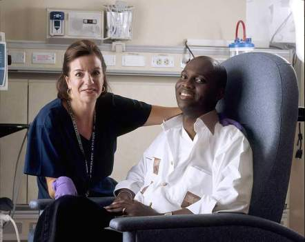 A Caucasian female nurse poses with an African-American male after he receives chemotherapy.