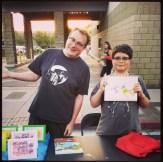 Logan and his art teacher at a cartooning art fair event