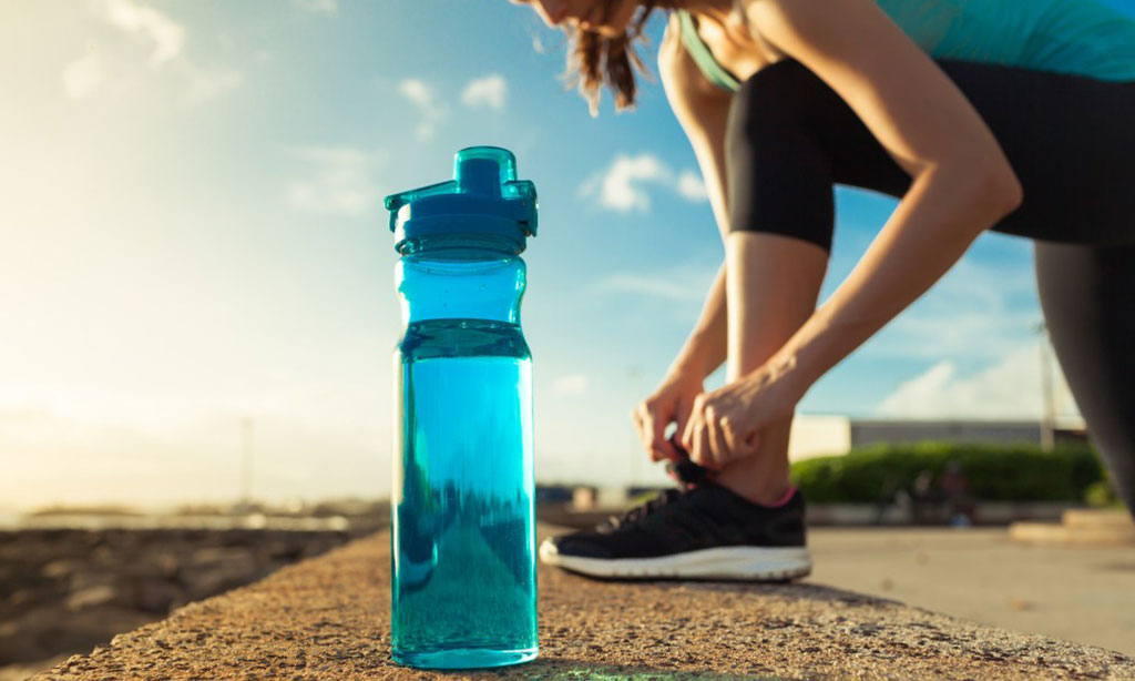 Female runner tying her shoe next to bottle of water.