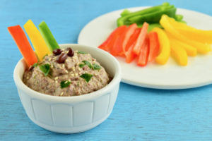 Adzuki bean dip with red, yellow and green bell pepper sticks on blue background