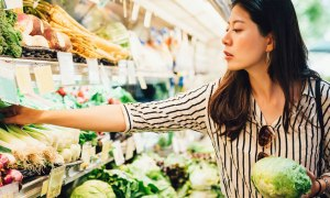 woman at marketplace buying vegetables