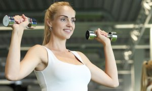 Sporty young woman with dumbbells