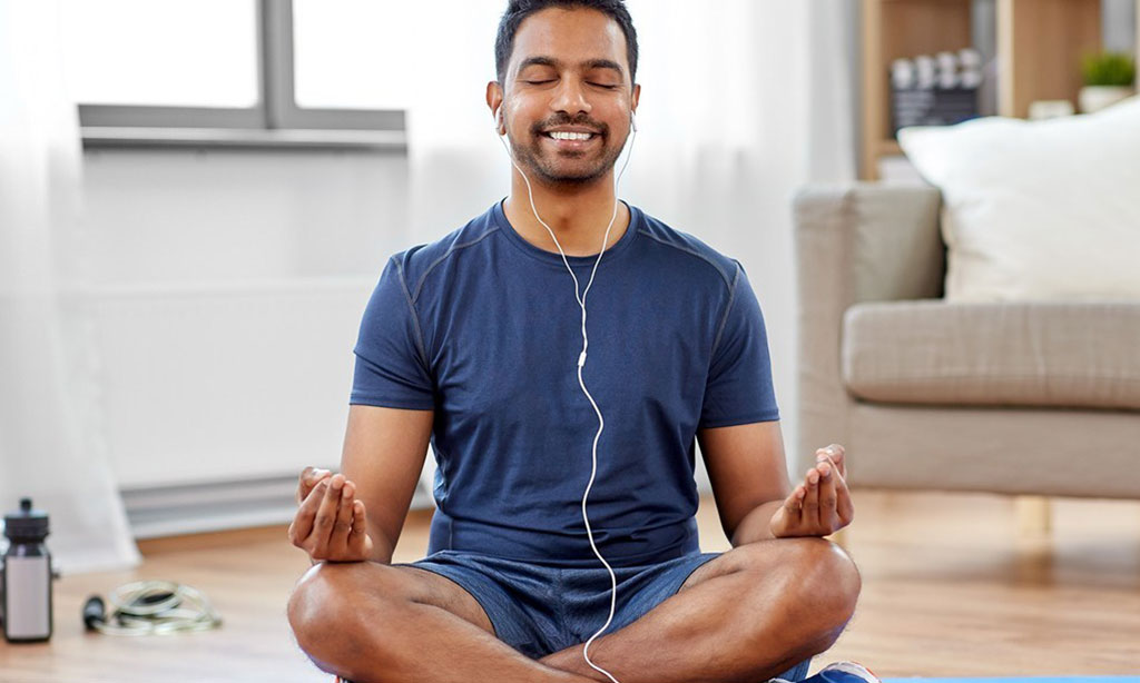 man in earphones listening to music on smartphone at home