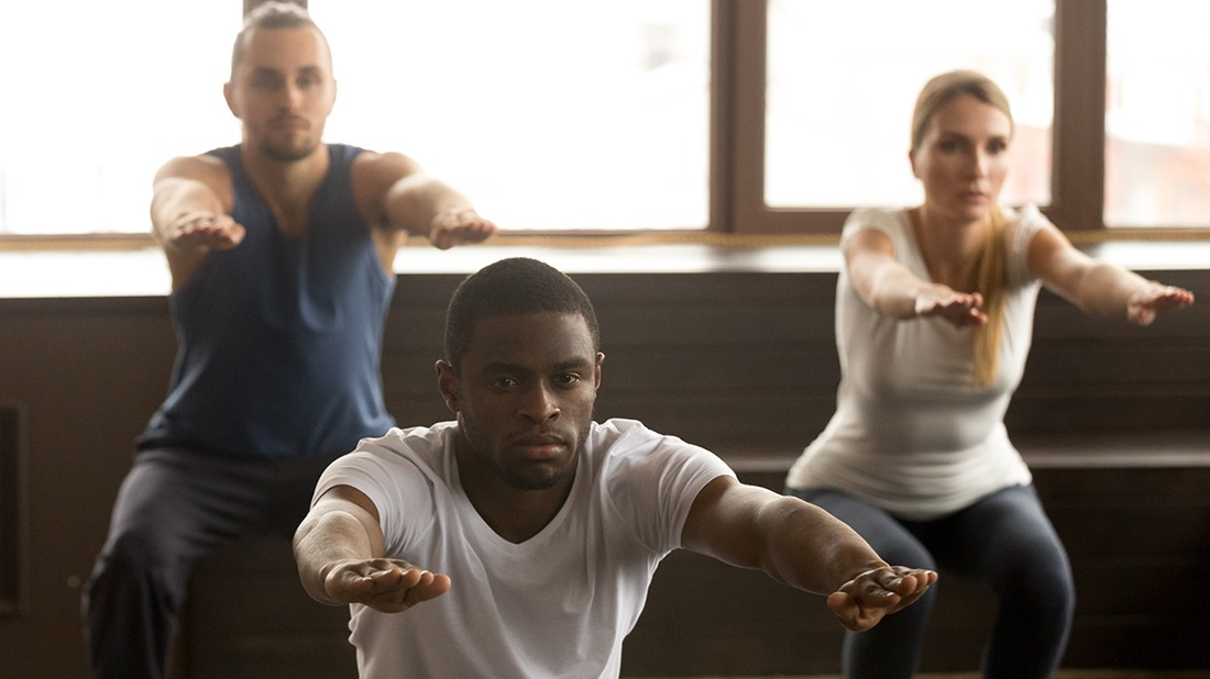 Young african american man doing squat exercise at group fitness training, sporty black guy focused on self-improvement working out with diverse active people in gym studio during routine session