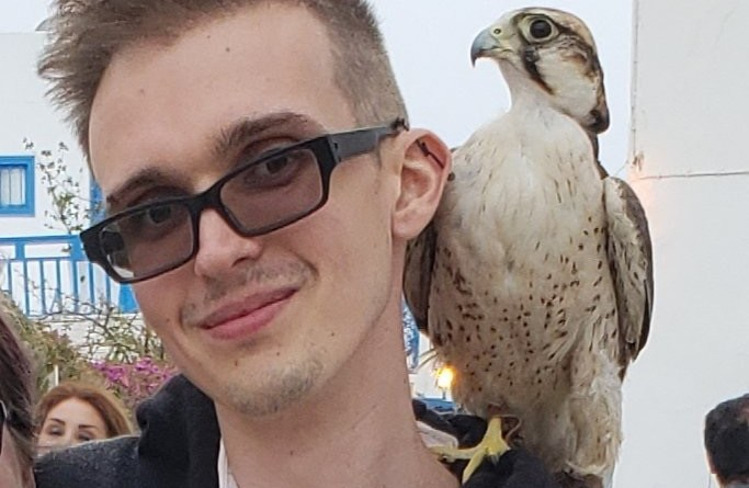 Man wearing glasses smiling at camera with a large bird on his shoulder.