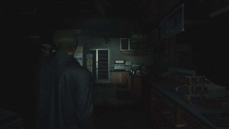 Leon walking in a dark gas station convenience store, holding a flashlight.