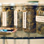 A rolling tray on a glass table with Cannabis in glass jars in the background
