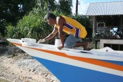A WAM trainee paints some finishing touches to the canoe. 039
