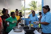 WAM Trainees Tine Lanwe, Helenty Hemos, and Naggie Kiluwe getting a cooking lesson. Photo: Tolina Tomeing