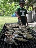 Trainee Scamyo Namdrik cooking fish caught. Photo: Alson Kelen