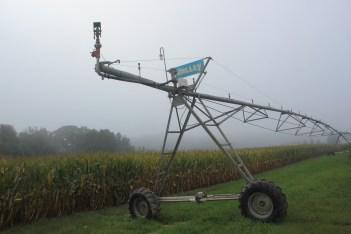 Irrigator next to corn field