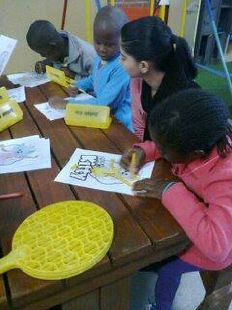 etv staff colouring books with kids at CANSA TLC Nicus Lodge