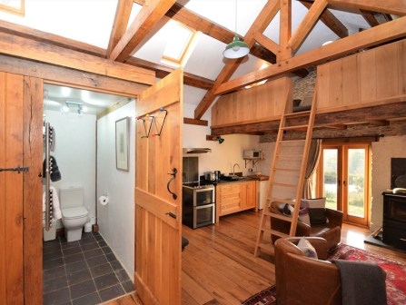 An image inside our beautiful converted barn showing the mezzanie snug and bathroom