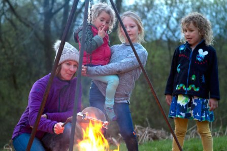 A photo of a mother and children cooking around the campfire in the glamping field