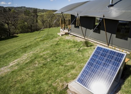An outside view of the safari tent and solar panel
