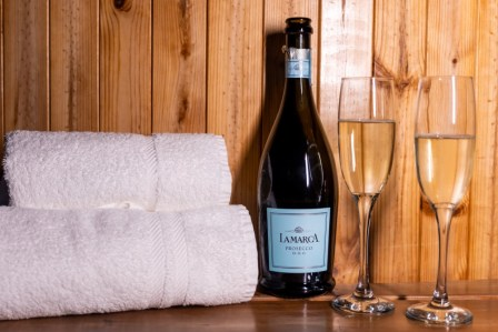 A bottle of prosseco, glasses and towels on the steps of the hot tub