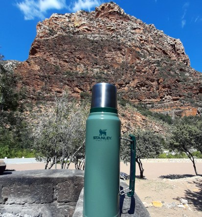 Stanley flask pictured against the backdrop of the majestic Meiringspoort.