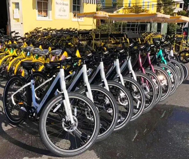 A line of bicycles in front of a yellow building