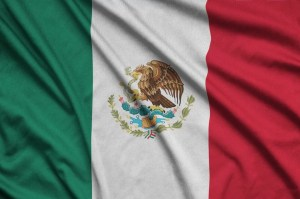 Mexico flag is depicted on a sports cloth fabric with many folds.