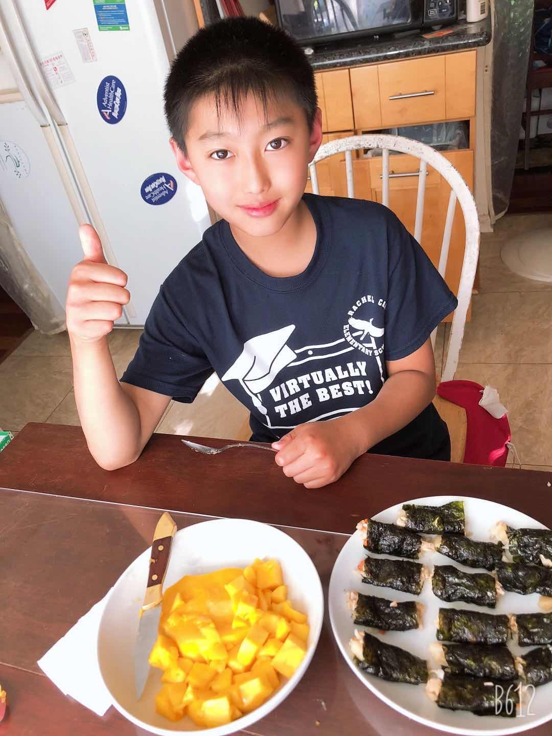 A young boy sitting at a table with a plate of food  Description automatically generated