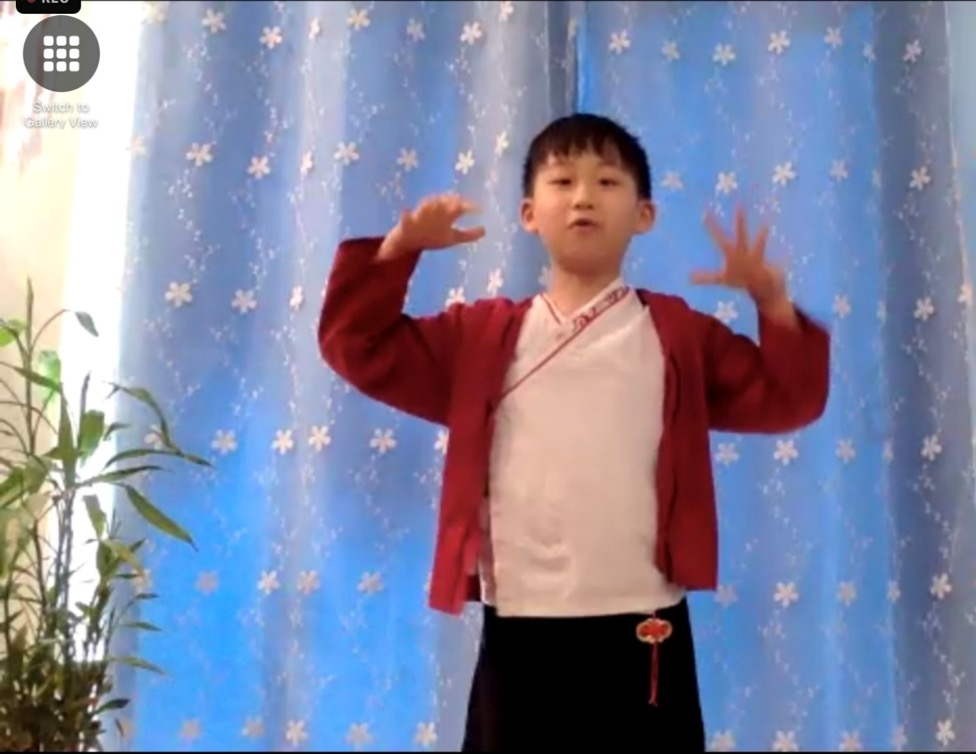 A child standing in front of a blue curtain  Description automatically generated with low confidence
