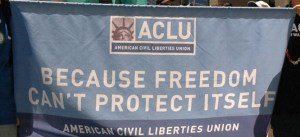 "ACLU Flag with ""Because Freedom Doesn't Protect Itself"" printed on it"