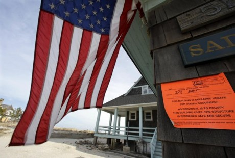 "In this Jan. 3, 2013, file photo, an unsafe for human occupancy sticker is attached to a home that was severely damaged by Superstorm Sandy in Bay Head, N.J. Conservatives and watchdog groups are mounting a ""not-so-fast"" campaign against a $50.7 billion Superstorm Sandy aid package that Northeastern governors and lawmakers hope to push through the House the week of Jan. 14, 2013. Their complaint is that lots of that money actually will go toward recovery efforts for past disasters and other projects unrelated to the late-October storm. The measure bill includes $150 million for what the Commerce Department described as fisheries disasters in Alaska, Mississippi and the Northeast, and $50 million in subsidies for replanting trees on private land damaged by wildfires. (AP Photo/Mel Evans)"