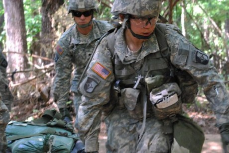 Capt. Sara Rodriguez, 26, of the 101st Airborne Division, carries a litter of sandbags during the Expert Field Medical Badge training at Fort Campbell, Ky. The Pentagon is lifting its ban on women serving in combat, opening hundreds of thousands of front-line positions and potentially elite commando jobs after generations of limits on their service, defense officials said Wednesday, Jan. 23, 2013. (AP Photo/Kristin M. Hall, File)