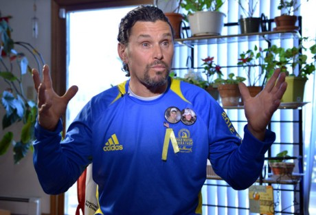 Carlos Arredondo speaks to a reporter in his home in the Roslindale neighborhood of Boston, Wednesday, April 17, 2013. Arredondo, a peace activist whose son was killed during the Iraq war, was handing out flags nearby at the time of the explosions and assisted victims after a pair of bombs exploded at the finish line of the Boston Marathon. (AP Photo/Josh Reynolds)