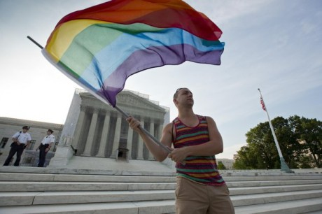 Gay rights advocate Vin Testa waves a rainbow flag in front of the Supreme Court at sun up in Washington, Wednesday. (AP Photo/J. Scott Applewhite)