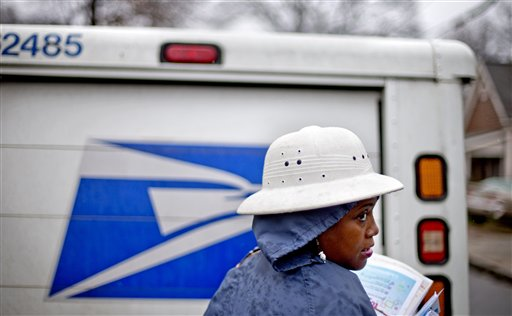Postal Service letter carrier Jamesa Euler, delivers mail in the rain in the Cabbagetown neighborhood, in Atlanta. (AP Photo/David Goldman)