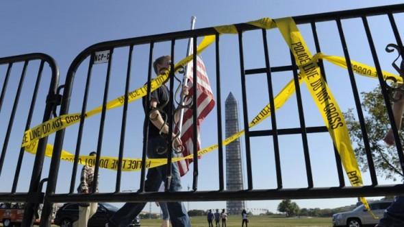 Pedestrians walk past a barricade preventing them from entering the World War II Memorial in Washington.  (AP Photo/Susan Walsh)