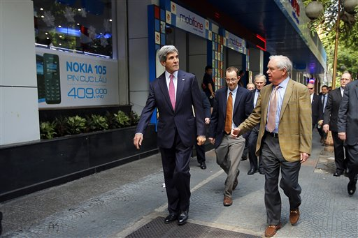 U.S. Secretary of State John Kerry, left, and his friend and fellow Vietnam War veteran Tommy Vallely, right, walk along a street in Ho Chi Minh City.  (AP Photo/Brian Snyder, Pool)