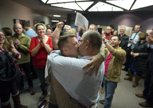 Chris Serrano (left) and Clifton Web kiss after marriage in Salt Lake City. (AP/Kim Raff)