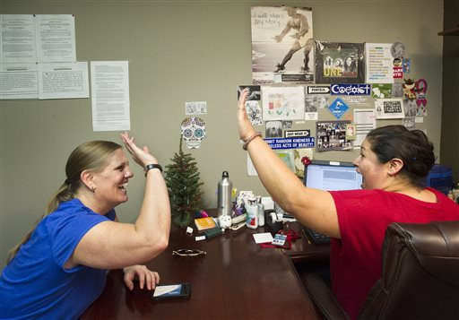 Lisa Donlea, 41, of Irvine, left, and Susan Roberts, a certified enrollment officer, celebrate after working on Donlea's federal health insurance exchange enrollment online for one hour and 47 minutes at the Irvine AIDS Services Foundation where Roberts is a housing case manager. (AP Photo/The Orange County Register, Cindy Yamanaka)