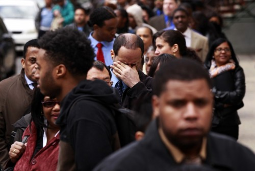 A man rubs his eyes as he waits in a line of jobseekers, to attend the Dr. Martin Luther King Jr. career fair held by the New York State department of Labor in New York. (REUTERS/Lucas Jackson)
