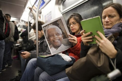 A subway rider in New York reads a newspaper featuring news of the death of South African leader Nelson Mandela.   (AP Photo/John Minchillo, File)