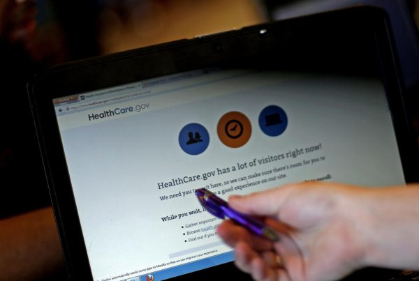 Elizabeth Rich points to a web page for the Affordable Care Act as she helps people sign up for health insurance at Swope Health Services in Kansas City.  (AP Photo/Charlie Riedel)