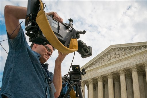 A videojournalist sets up outside of the Supreme Court Tuesday,   (AP Photo/J. David Ake)