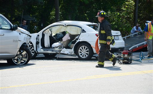 Firefighter taking equipment back to the truck after a woman, pinned in her white vehicle, was rescued by the jaws of life, in Kinston, N.C.  (AP Photo/Daily Free Press, Janet S. Carter)