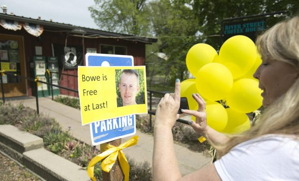 Diane Walker takes a picture of a sign celebrating U.S. Army Sgt. Bowe Bergdahl's release in front of Zaney's coffee shop in Hailey, Idaho.  (AP Photo/The Idaho Statesman, Kyle Green)