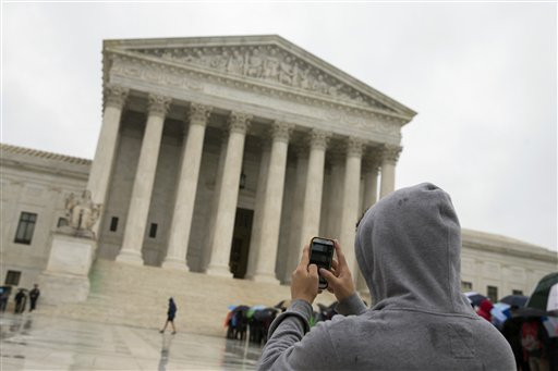 Supreme Court visitor using his cellphone to take a photo of the court in Washington.  (AP Photo)
