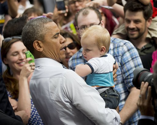 President Barack Obama picks-up a child while greeting members of the audience after speaking on the economy, Friday  (AP Photo/Pablo Martinez Monsivais)