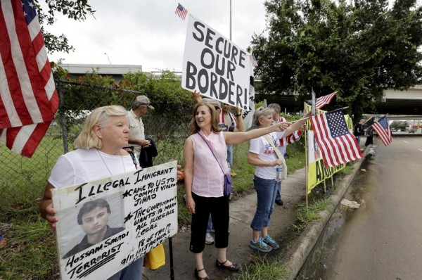 Demonstrators hold signs and flags outside the Mexican Consulate on Friday (AP Photo/David J. Phillip)