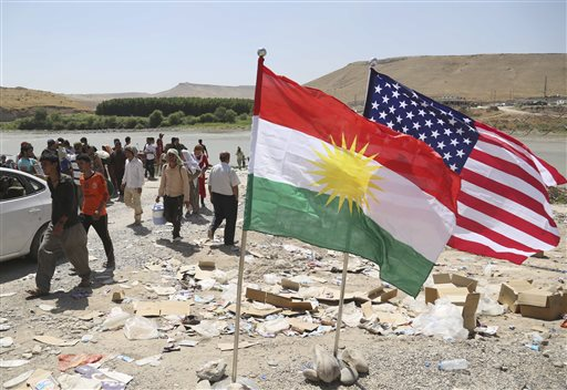 U.S. and Kurdish flags flutter in the wind while displaced Iraqis from the Yazidi community cross the Syria-Iraq border  (AP Photo/ Khalid Mohammed)