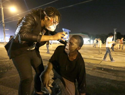 A man is helped ease the effects of tear gas  (AP Photo/Charlie Riedel)