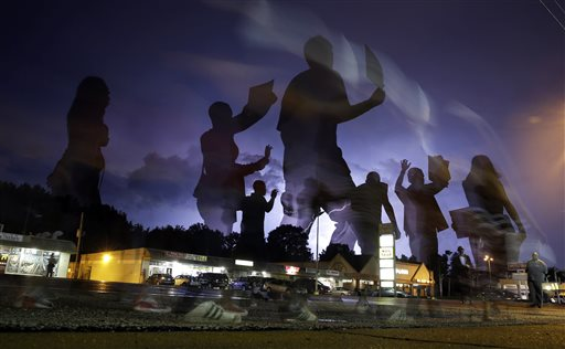 Protesters march in the street as lightning flashes in the distance in Ferguson  (AP Photo/Jeff Roberson)