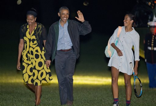 President Barack Obama, center, and first lady Michelle Obama, left, walk with their daughter Malia, right, across the South Lawn of the White House  (AP Photo/Pablo Martinez Monsivais)